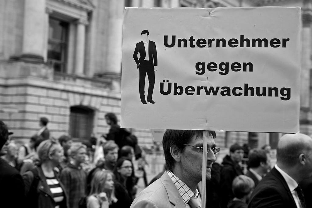 "A protester holds a sign saying ""Entrepreneurs against surveillance"" at the yearly 'Freiheit statt Angst' [Freedom instead of Surveillance] demonstration in Berlin, August 2014 (Source: Markus Winkler [CC])."